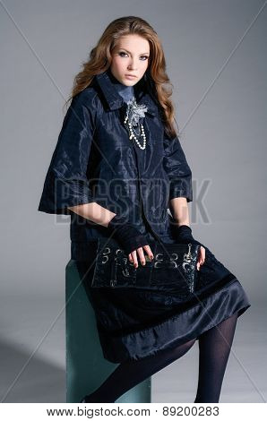 Full body fashion model in fashion dress holding purse sitting cube