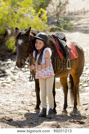 Young Girl 7 Or 8 Years Old Holding Bridle Of Little Pony Horse Smiling Happy Wearing Safety Jockey