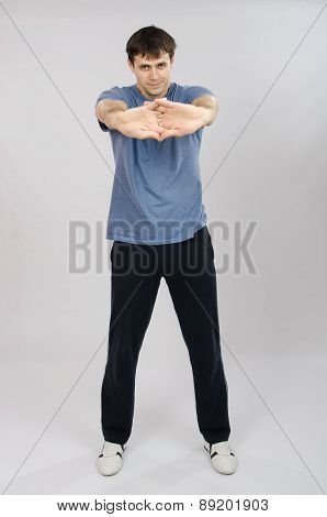 Young Man Pulls The Arm Muscles
