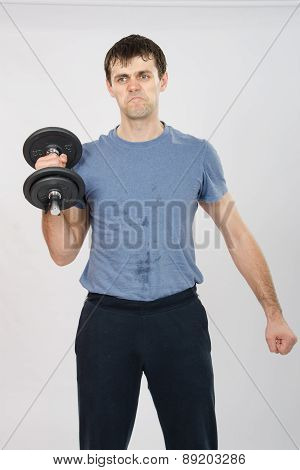 Athlete With A Dumbbell Effort Raises His Right Hand