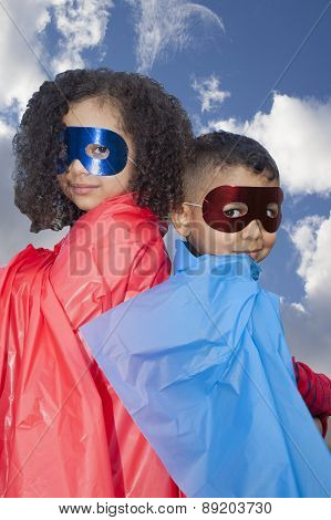 Little Boy And Girl Superheros Against Blue Sky