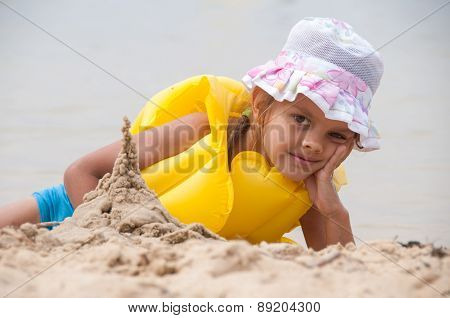 Five Year Old Girl On The Beach Sand Built Tower