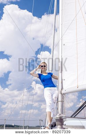 Positive Caucasian Woman Sailing On Yacht And Standing On Upper Deck. Positive Facial Expression.