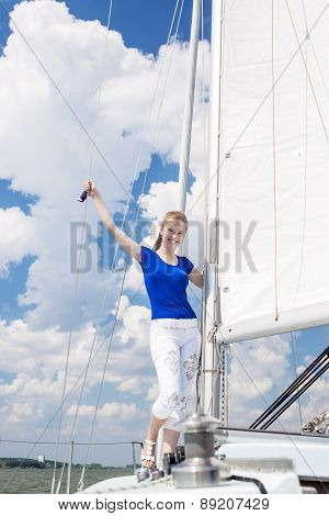 Positive Caucasian Woman Sailing On Yacht And Standing On Upper Deck. Positive Facial Expression