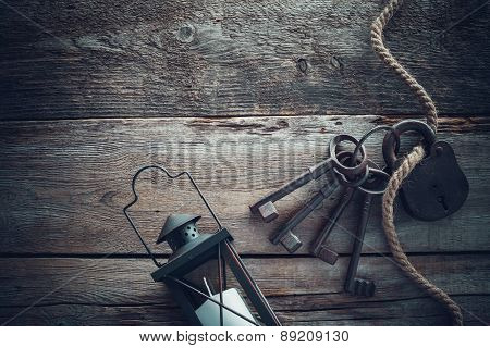 Old Rusty Lock With Keys, Vintage Lamp, Bottle From Clay And Rope On Wooden Board. Top View.