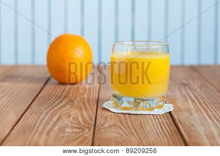 Glass of freshly pressed orange juice with whole fruit on wooden table