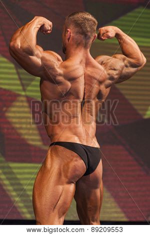 Bodybuilder On Stage Demonstrating His Body and Muscles