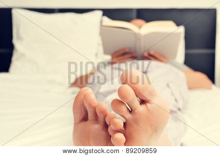 a young caucasian man in pajamas reading a book in bed