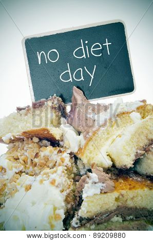 closeup of some pieces of cake and a signboard with the text no diet day written in it