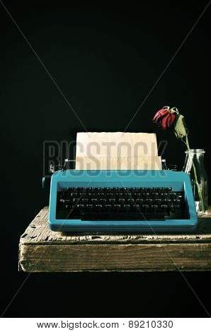 an old blue typewriter with a bank page in its roller and a wilted red rose in a glass vase on a rustic wooden table, against a black background