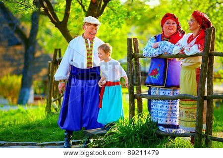 Happy Ukrainian Family In Traditional Costumes Talking Outdoor
