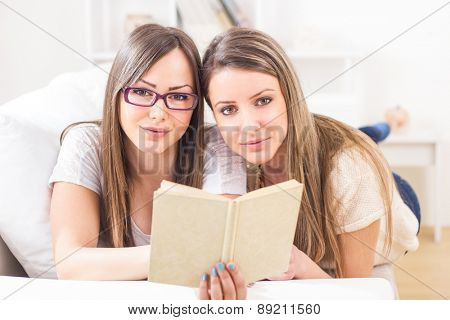 Two girl friends enjoying free time reading book