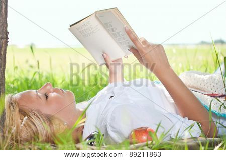 Young girl outside lie in park reading book, enjoy nice sunny day