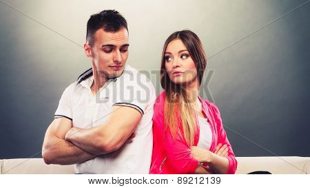 Young Couple After Quarrel Sitting On Sofa Back To Back
