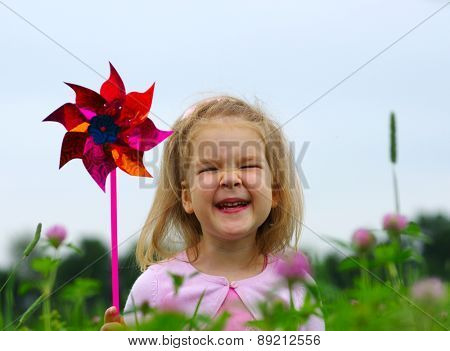 Cute little girl on the meadow in spring day. Child running on field . Child with arms outstretched. Freedom concept.