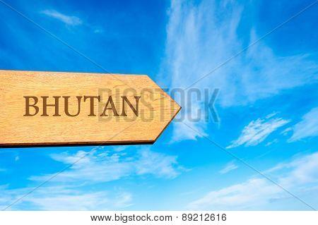 Wooden arrow sign pointing destination BHUTAN