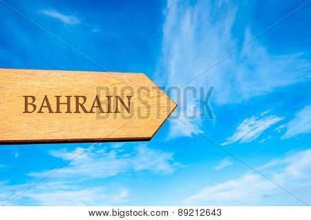 Wooden arrow sign pointing destination BAHRAIN