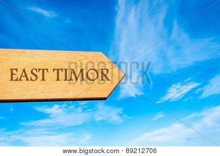 Wooden arrow sign pointing destination EAST TIMOR