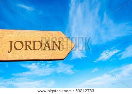 Wooden arrow sign pointing destination JORDAN
