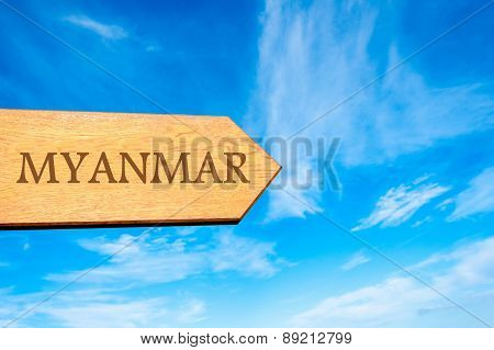 Wooden arrow sign pointing destination MYANMAR