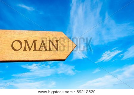 Wooden arrow sign pointing destination OMAN