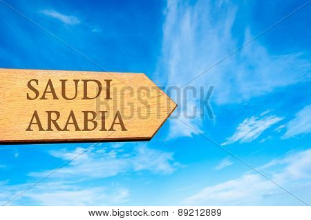 Wooden arrow sign pointing destination SAUDI ARABIA