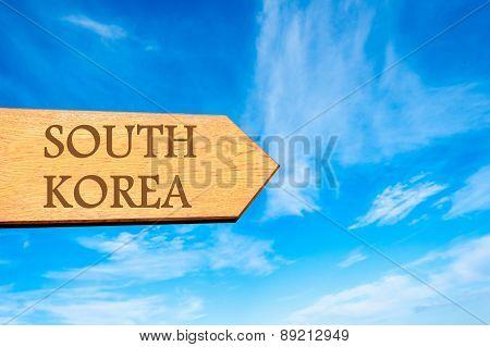 Wooden arrow sign pointing destination SOUTH KOREA