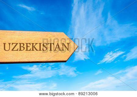 Wooden arrow sign pointing destination UZBEKISTAN