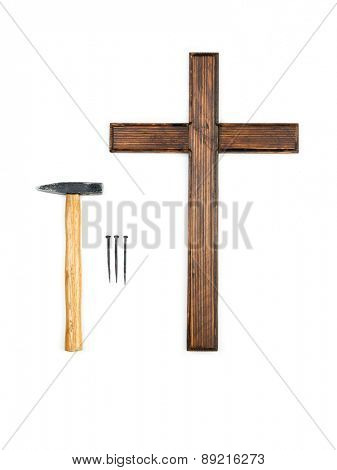 Wooden empty cross, hammer and three nails - do-it-yourself crucifying concept