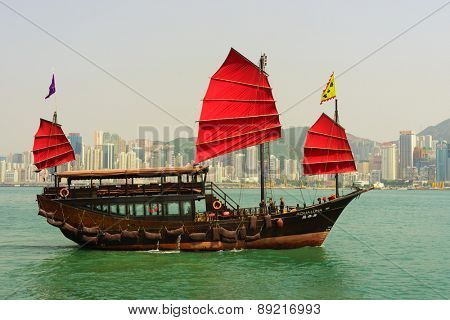 HONG KONG - APRIL 16, 2015: sailboat across Victoria Harbour. Victoria Harbour is a natural landform harbour situated between Hong Kong Island and Kowloon in Hong Kong.