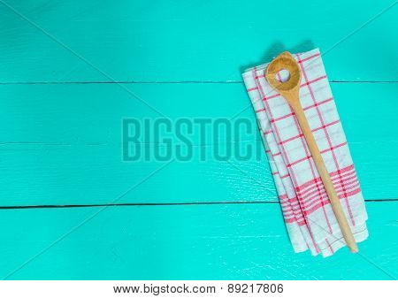 Wooden Spoon And Kitchen Towel On Turquoise Wooden Background