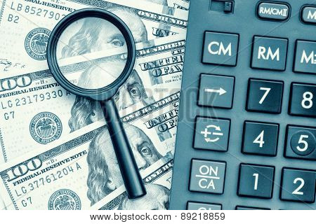 Business accounting or financial audit - Stack of dollar bills with a calculator and a magnifying glass