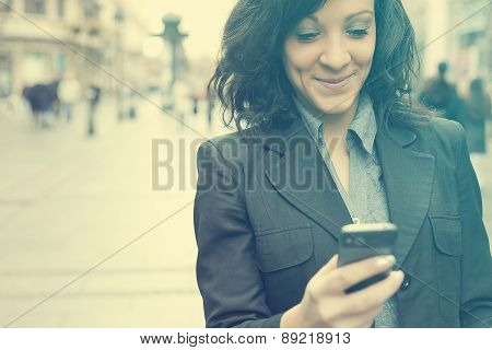Businesswoman With Smartphone Walking On Street
