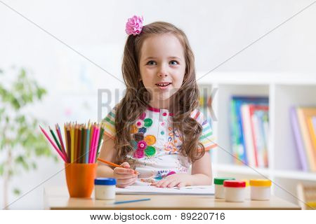 Cute little preschooler child drawing at house