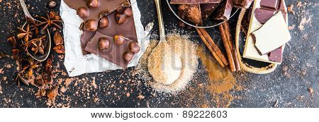 Chocolate in plates and spices in the spoons on black table