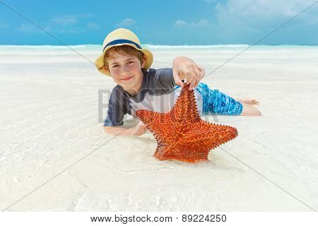 Boy and starfish on a tropical beach