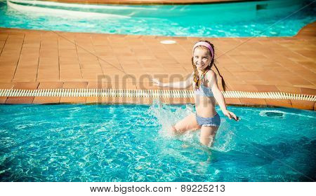 little happy girl swims in the pool
