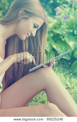 Beautiful Woman With Tablet Computer In Park Garden