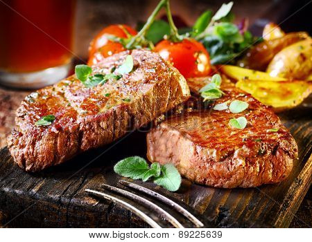 Succulent thick juicy portions of grilled fillet steak served with tomatoes and roast vegetables on