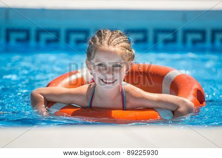 happy cute little girl swims with a lifeline in the pool in  summer