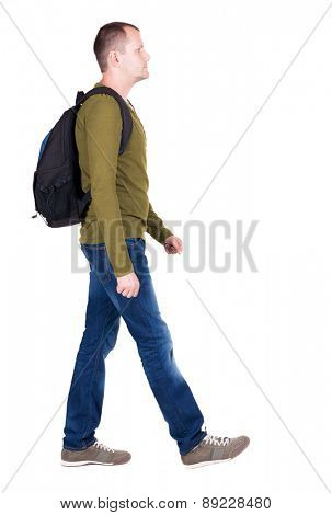back view of walking  man with backpack.  brunette guy in motion. backside view of person.  Rear view people collection. A man in a green jacket is wearing a backpack on his back.