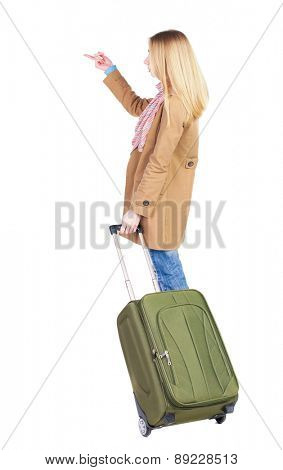Back view of  pointing woman with suitcase looking up. Standing young girl. Rear view people collection.  backside view of person. Isolated over white background. The woman goes on a mission to