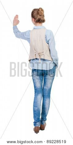 back view of woman. Young woman in vest presses down on something. Isolated over white background. Rear view people collection. backside view of person. she holds his hand open, palm forward