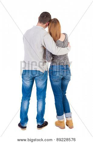 Back view of young embracing couple  hug and look into distance. Rear view people collection.  backside view of person.  Isolated over white background. The girl clung to shoulder of her boyfriend.