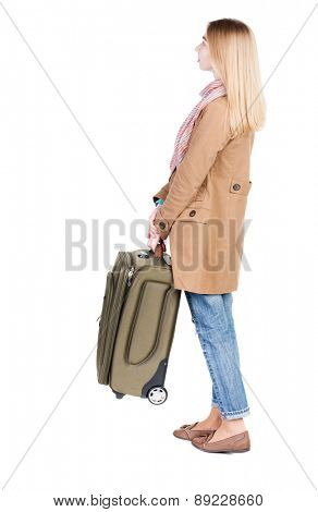 Back view of woman with suitcase looking up. Standing young girl. Rear view people collection.  backside view of person. Isolated over white background. Waiting for a girl barely holding suitcase.