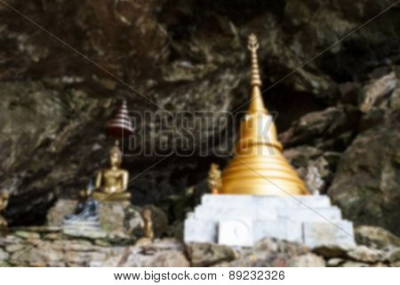 Blurry Image Of Buddha Statue And Golden Pagoda In The Cave