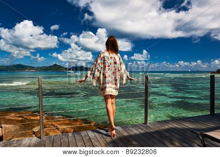 Woman with sarong on a tropical beach jetty at at Seychelles, La Digue.