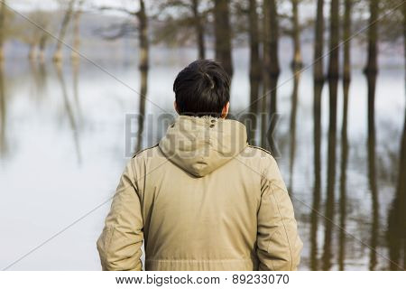 Man in jacket observing the river from the shore