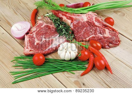 fresh meat : raw beef spare ribs with thyme , red chili pepper , garlic , dill, and cherry tomato on wooden board