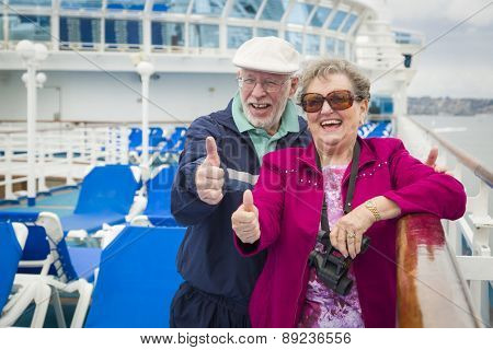Happy Senior Couple With A Thumbs Up On The Deck of A Luxury Passenger Cruise Ship.